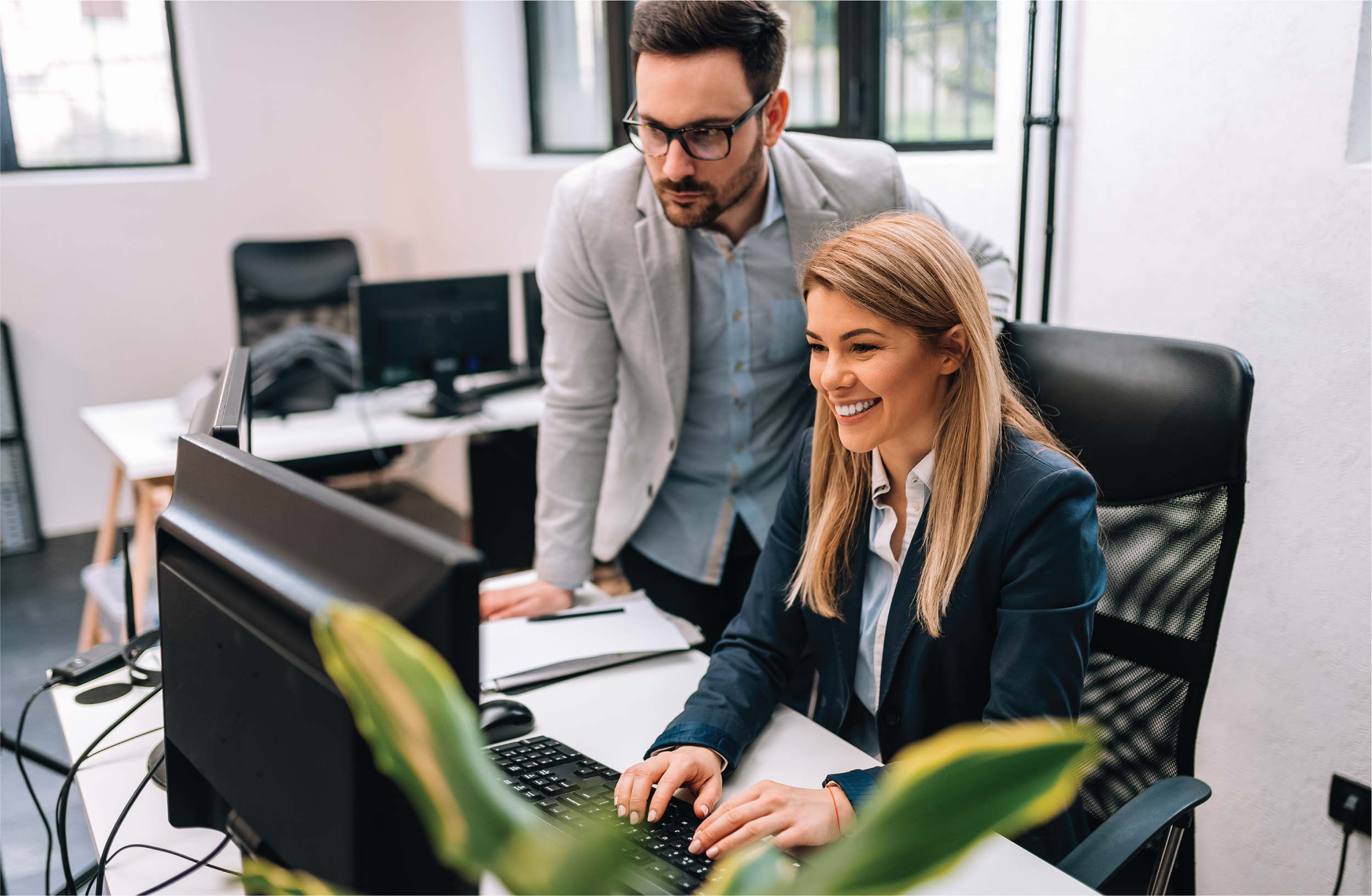 male executive boss supervising computer work of a young female employee | Botkeeper