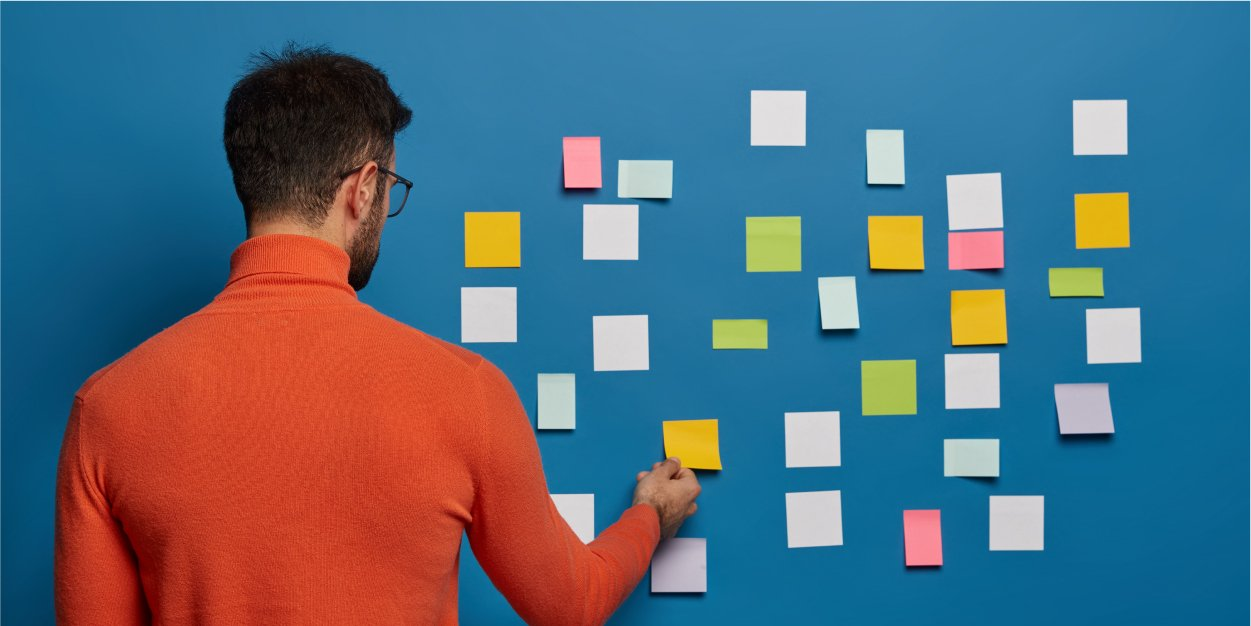 Man brainstorming growth strategy using sticky notes | Botkeeper | How Your Firm Defines CAS Will Determine Your Growth Strategy