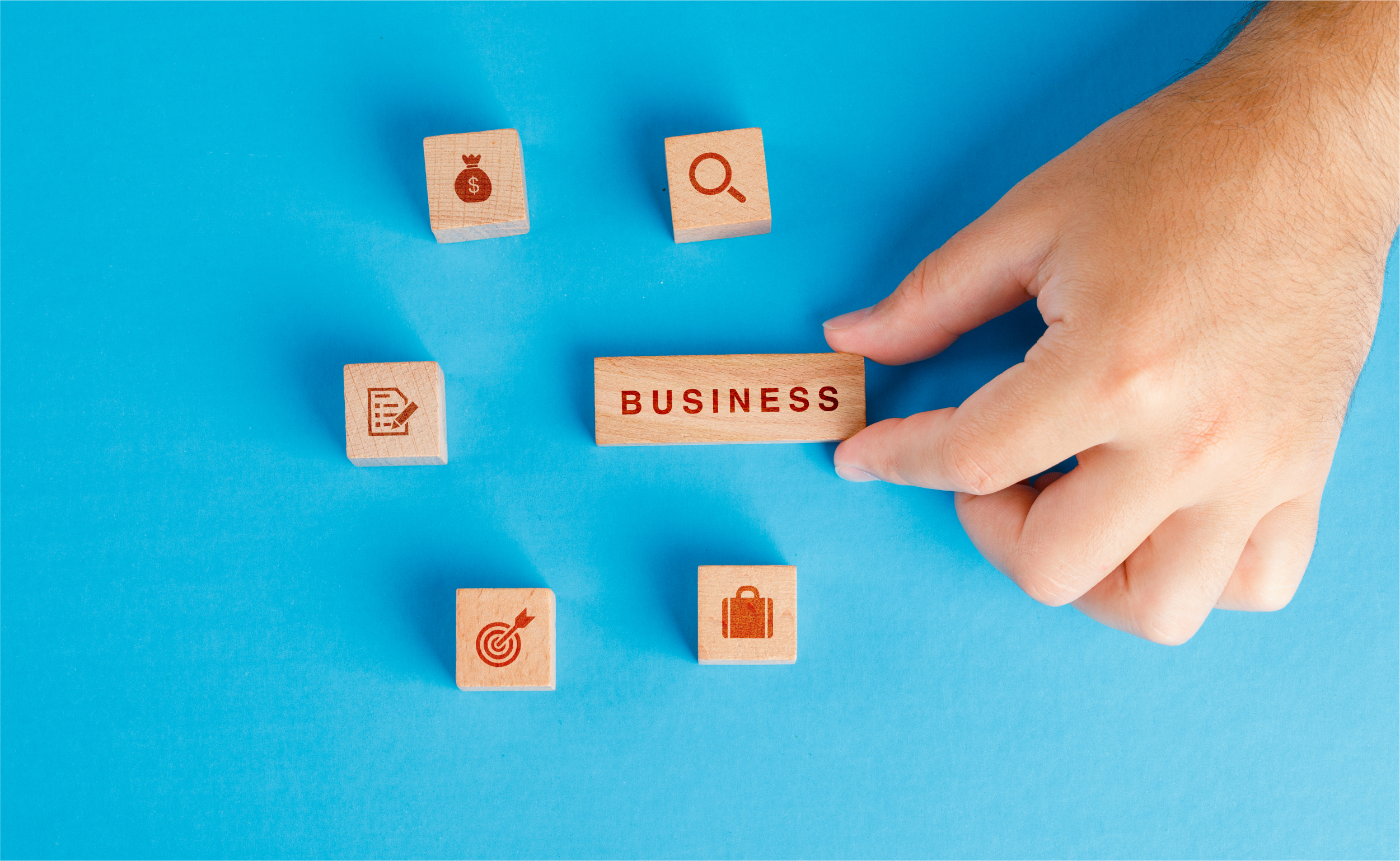 business-concept-with-icons-wooden-cubes-blue-table-flat-lay-hand-holding-wooden-block | botkeeper