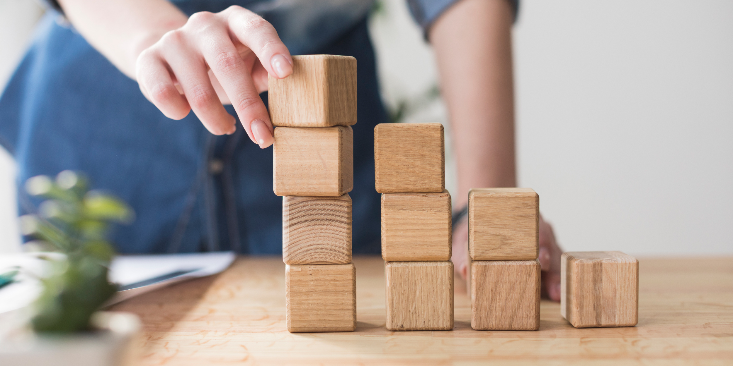 close-up-female-hand-stacking-wooden-block-desk-office_Blog copy