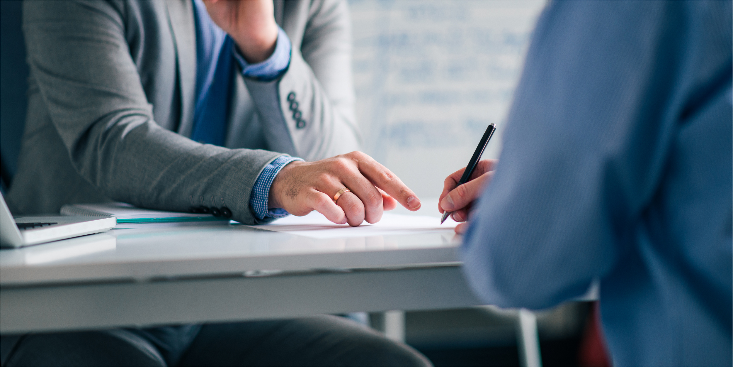 low-angle-image-two-men-formal-wear-sitting-desk-signing-agreement_Building CAS in 2021: What Your Firm Needs to Know to Get Started_Botkeeper