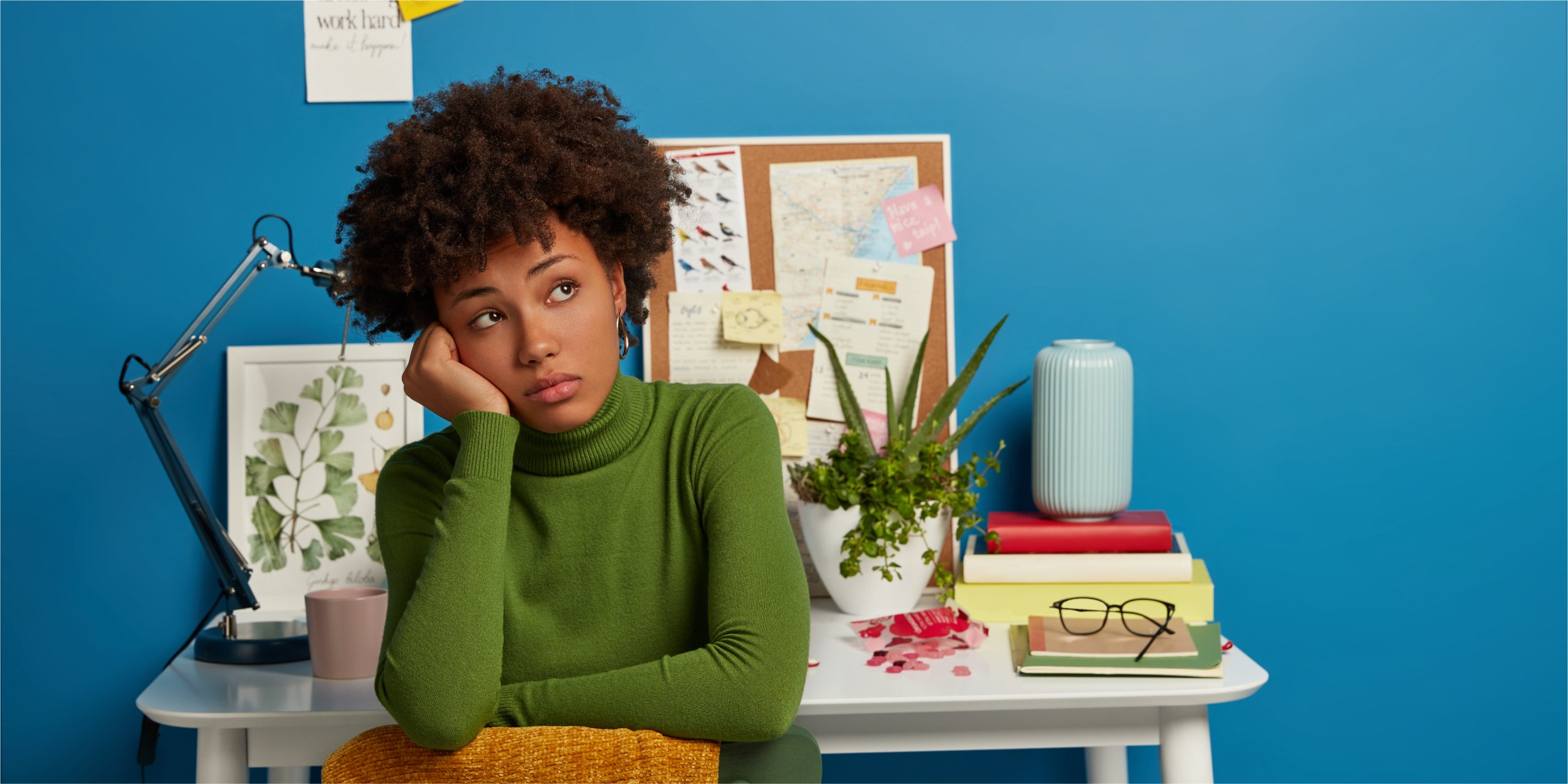 pensive-dark-skinned-lady-looks-away-dressed-green-turtleneck-has-rest-after-working-desktop-poses-home-against-blue-background_The Most Important Metric for Firm Growth Is Revenue Per Client—Here's Why_Botkeeper