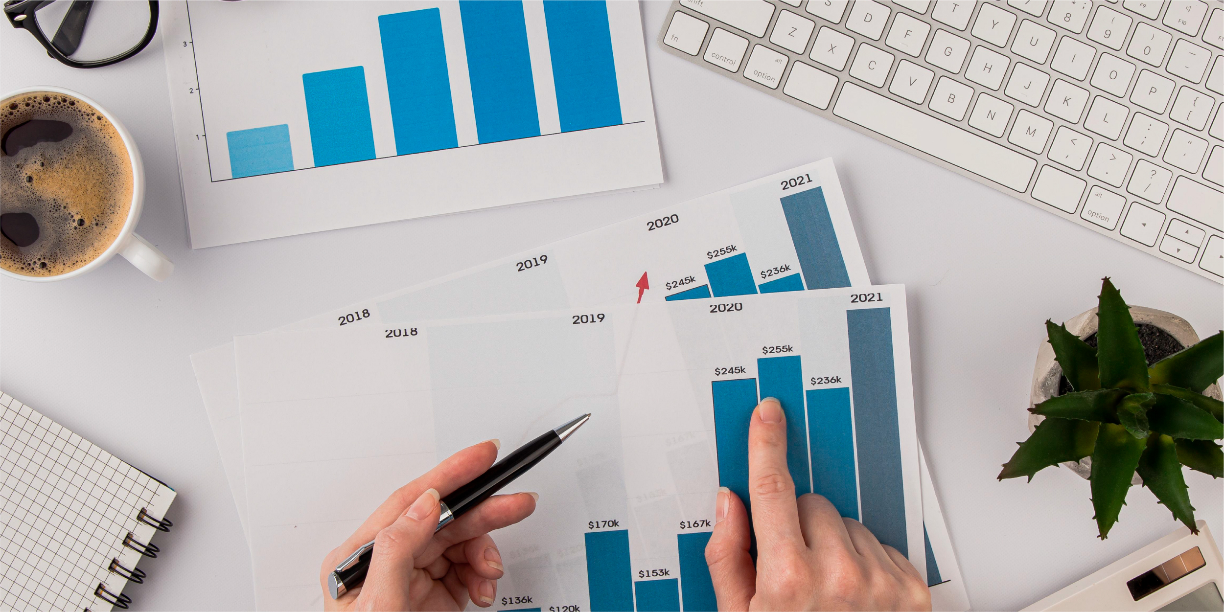 top-view-office-desk-with-growth-chart-hands_The Most Important Metric for Firm Growth Is Revenue Per Client—Here's Why_Botkeeper
