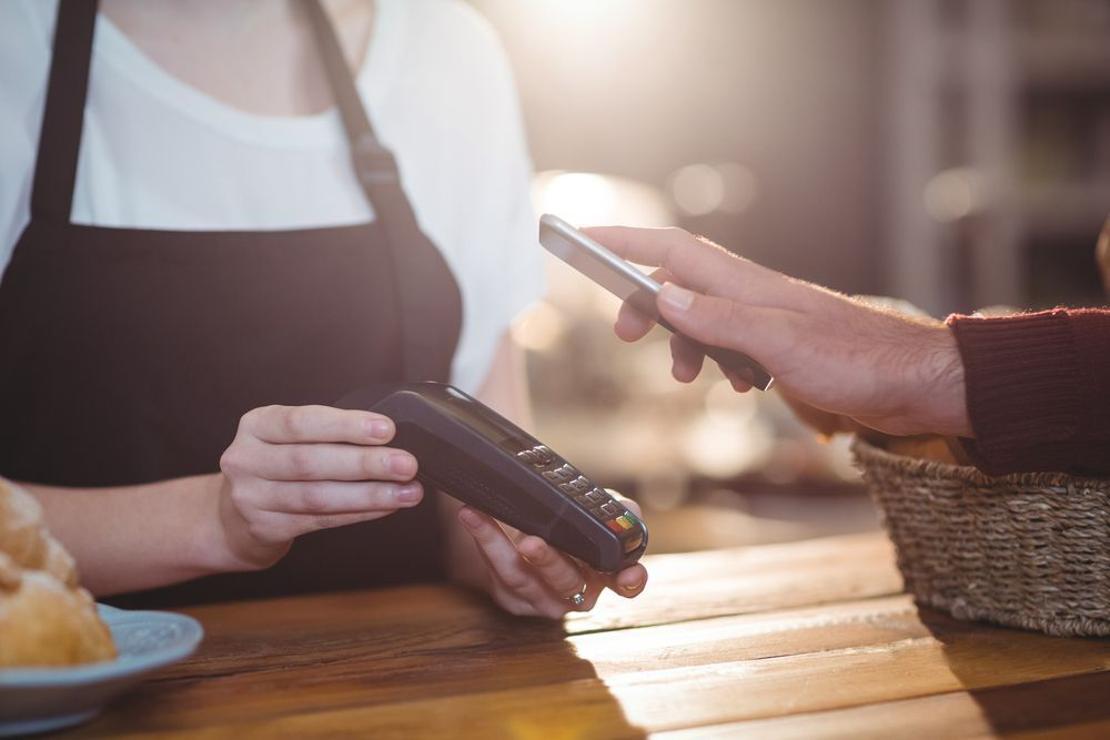Customer paying bill through smartphone using NFC technology in cafe | Botkeeper