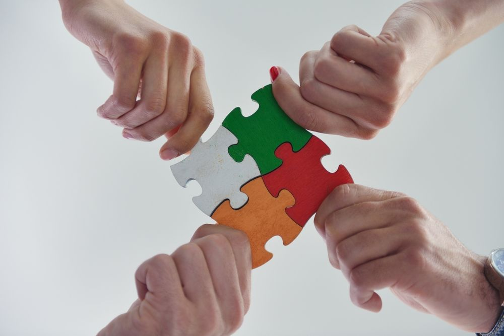 Group of business people assembling jigsaw puzzle and represent team support and help concept | Botkeeper