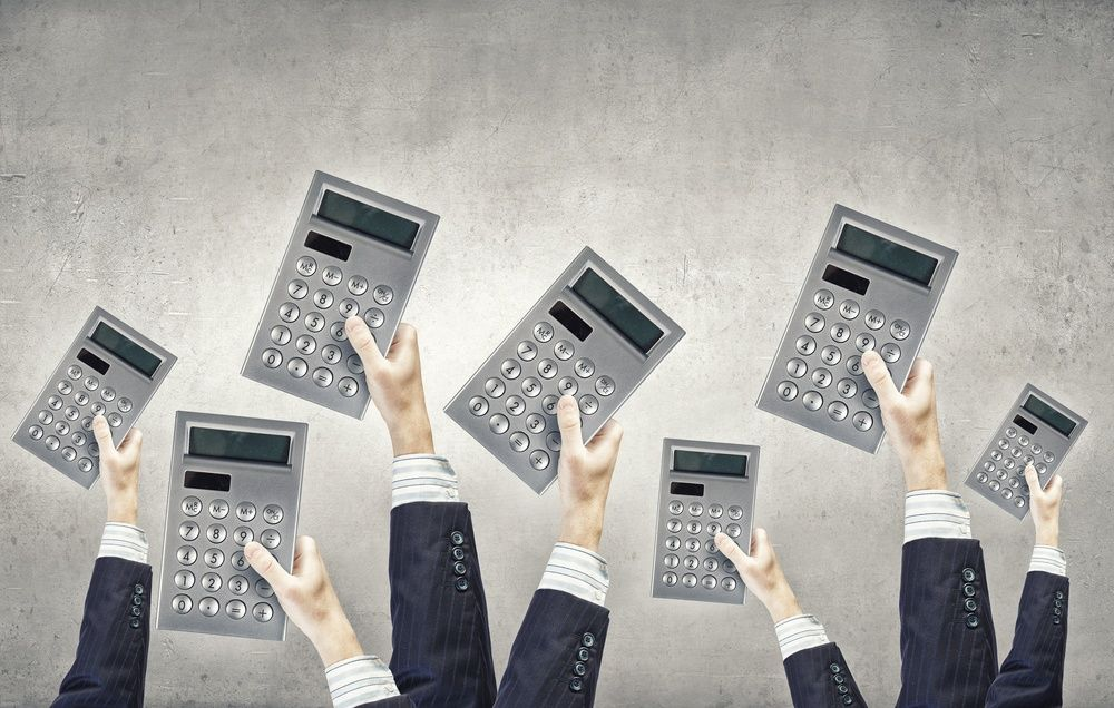 Many hands of business people holding calculators