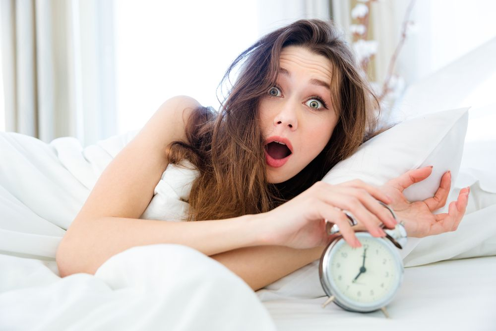 Shocked young woman waking up with alarm-1