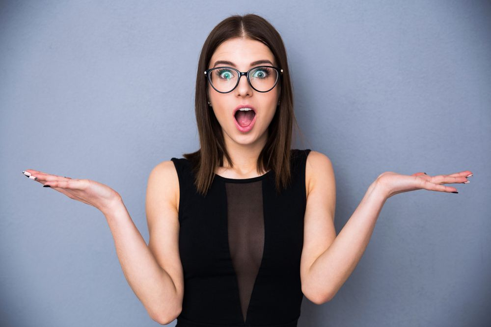 Young beautiful woman with facial expression of surprise standing over gray background. Wearing in trendy black dress and glasses. Looking at the camera | Botkeeper