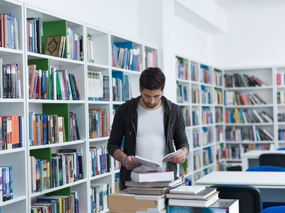portrait of student in collage school library, arab youth learning and reading book